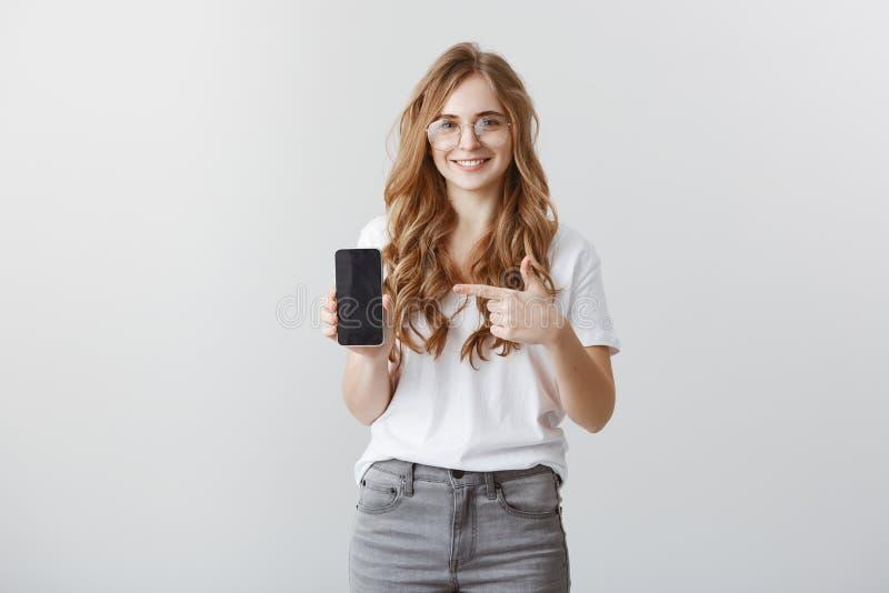 Ty no znajdowałeś telefonu lepiej Zadowolony atrakcyjny sklepowy asystent w modnych przejrzystych szkłach pokazuje smartphone zdjęcie royalty free