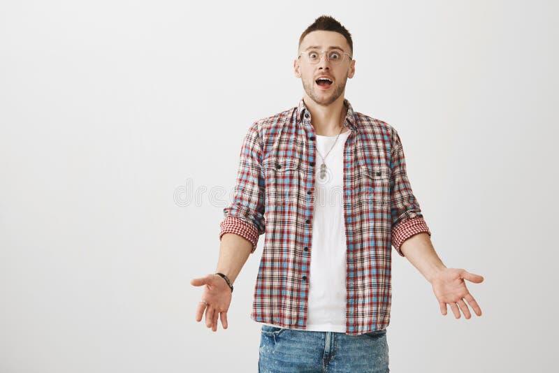 Ty szokowałeś ja z taki okropną wiadomością Studio strzał sfrustowany zdziwiony nieogolony mężczyzna wzrusza ramionami w modnych  zdjęcia stock