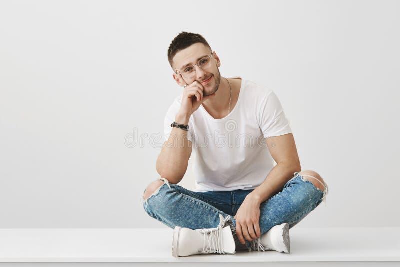 Ty w ten sposób zanudzasz Studio strzelający atrakcyjny caucasian nieogolony facet w szkłach, siedzący z krzyżować nogami na podł fotografia stock
