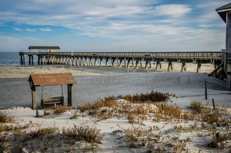 Tybee Island pier in Southern Georgia United States on the beach of the Atlantic Ocean, and a swing. Tybee Island pier in Southern Georgia United States on the royalty free stock photo