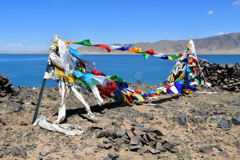 Tybet, buddysta zaznacza z mantrami przed świętym jeziornym półdupka Co jeziorem w lato słonecznym dniu obrazy royalty free