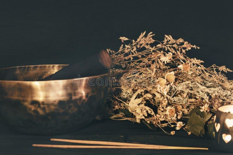 Tybetańska miska, suche zioła, kadzidło, płonąca świeca zdjęcia royalty free