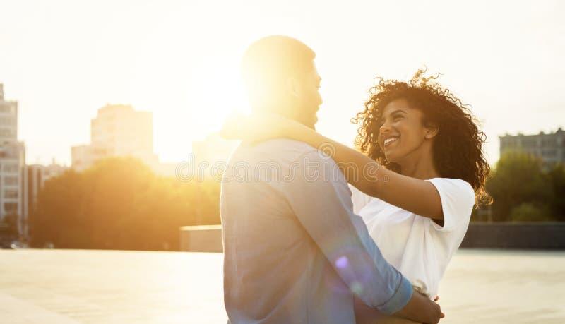 Tyck om ögonblicket Älska par som kramar på solnedgången arkivbild