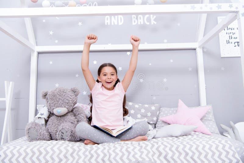 Tyck om begreppet Den lyckliga flickan tycker om att bli i säng Det lilla barnet med lyftta händer tycker om läseboken tyck om li royaltyfri foto
