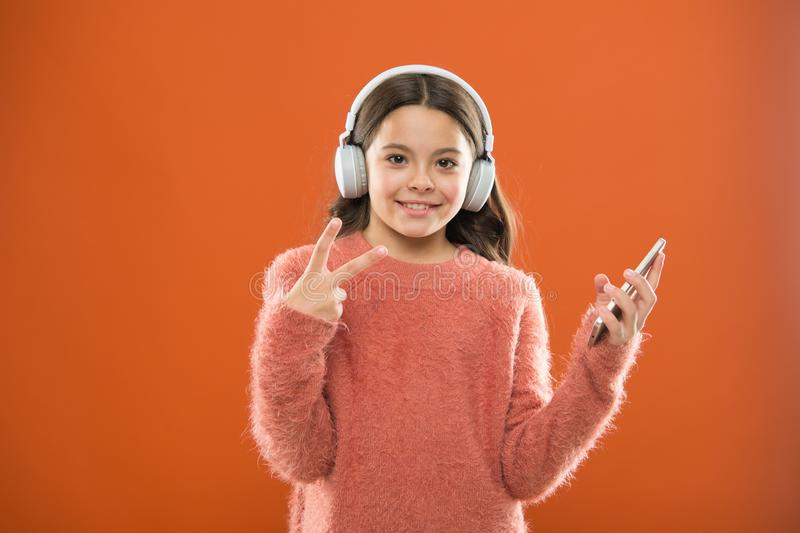Tyck om musikbegreppet Bästa musikapps som förtjänar a för att lyssna Flickabarnet lyssnar den moderna hörlurar och smartphonen f arkivbilder