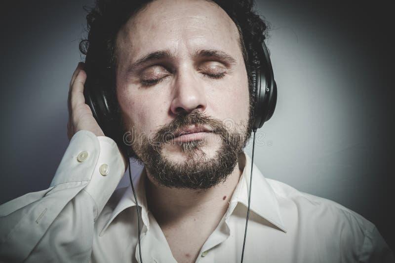 Tyck om musiken, mannen med intensivt uttryck, den vita skjortan royaltyfri foto
