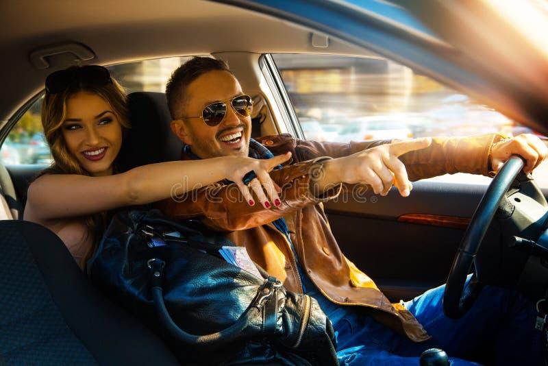 Tyck om roliga par för liv som kör bilen på hög hastighets- och punktfingret royaltyfri fotografi