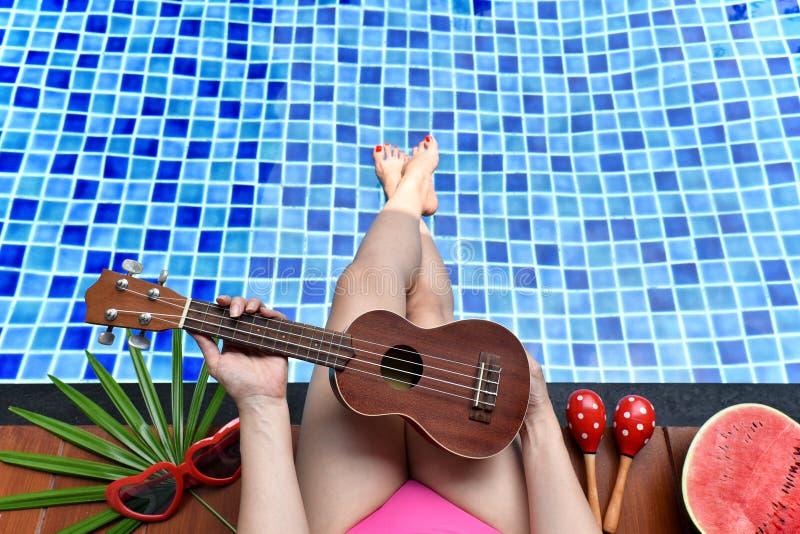 Tyck om sommarbrisferie, flickan som kopplar av nära simbassängen med vattenmelonfrukt royaltyfria bilder
