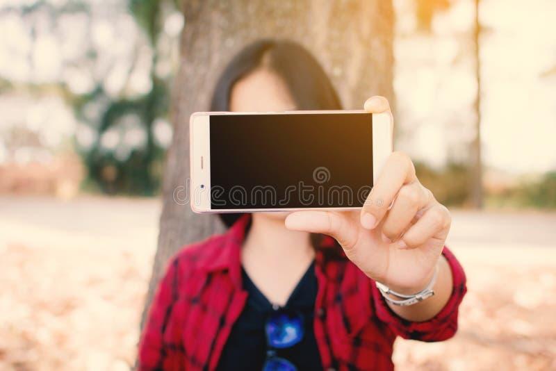Tycka om ögonblickskvinnan som använder smartphonesammanträde under det stora trädet parkera på arkivbild