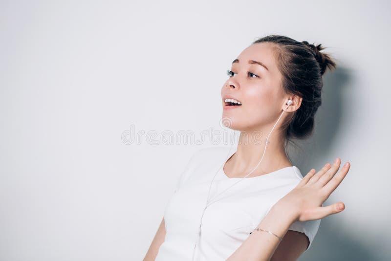 Tycka om det solitt Ståenden av den lyckliga unga kvinnan med vita hörlurar är lyssnande musik arkivfoton