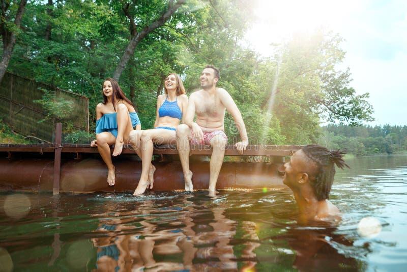 Tycka om flodpartiet med vänner Grupp av härliga lyckliga ungdomarpå floden tillsammans arkivbild