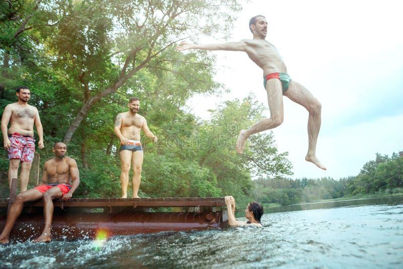 Tycka om flodpartiet med vänner Grupp av härliga lyckliga ungdomarpå floden tillsammans arkivfoto
