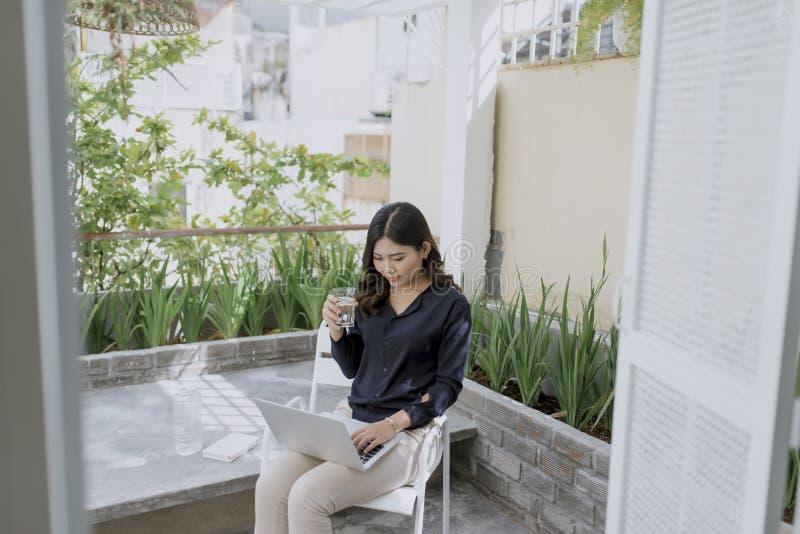 Tycka om hennes morgonkaffe H?rlig ung le kvinna som rymmer tekoppen och ser kameran, medan sitta i en stol p? henne arkivfoton