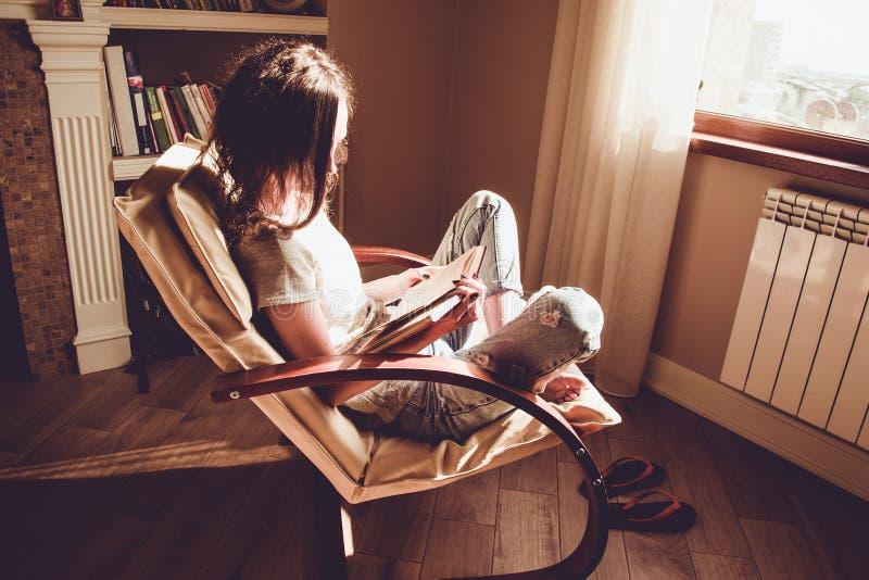 tycka om home tid Avslappnande bekväm modern stol för kvinna nära fönster som läser den pappers- boken Naturlig lampa hemtrevlig  royaltyfri fotografi