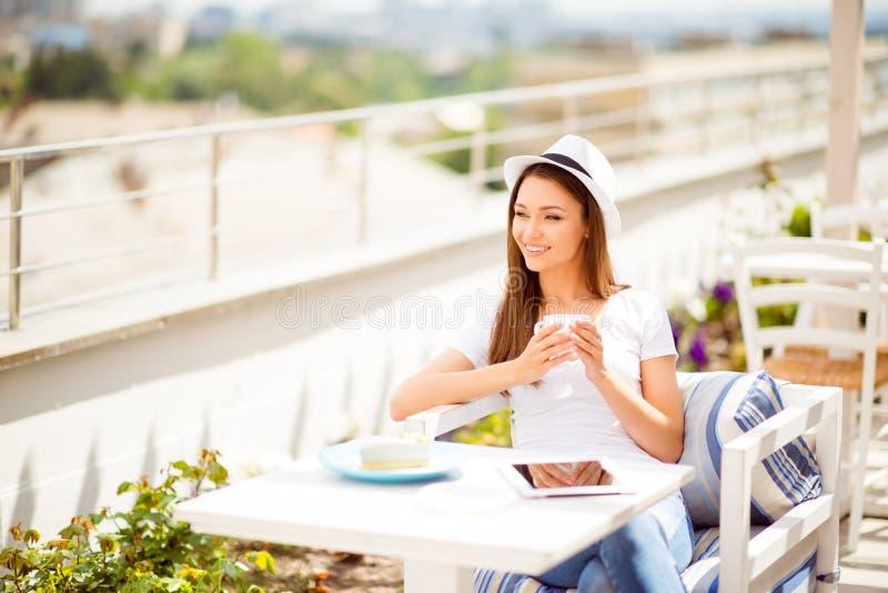 Tycka om kaffe på sommarsemestern på en öppen luft för taköverkant tänd restaurangen Den unga damen är så drömlik och avkopplad,  royaltyfri bild