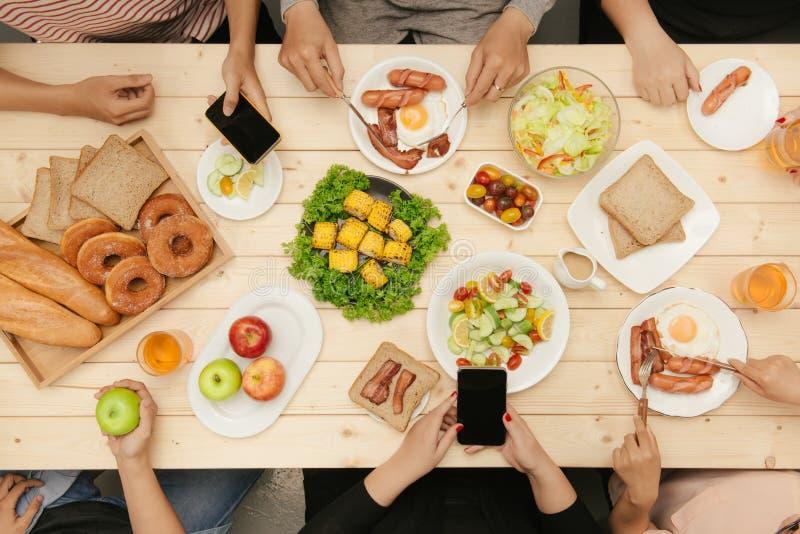 Tycka om matställen med vänner Bästa sikt av grupp människor som har matställen tillsammans, medan sitta på trätabellen royaltyfri bild