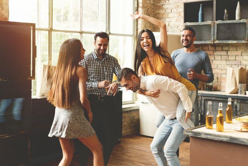 Tycka om partiet med bästa vän Gladlynta ungdomarsom dansar och dricker, medan tycka om hem partiet på köket arkivbilder