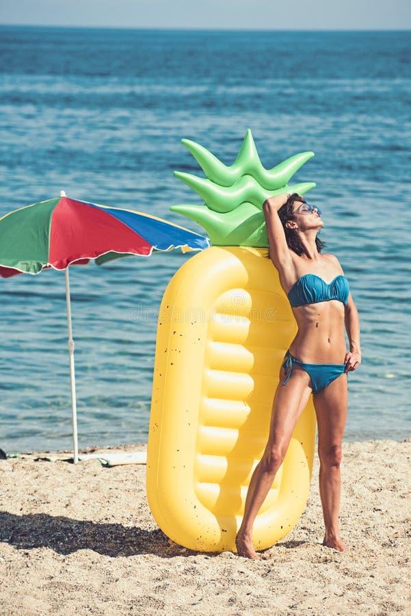 Tycka om solbränna härligt barn för kvinna för begreppspölsemester Slank ung kvinna i bikini på den gula luftmadrassen arkivfoto