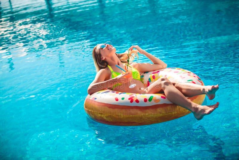 Tycka om solbr?nnakvinnan i bikini p? den uppbl?sbara madrassen i simbass?ngen royaltyfria foton