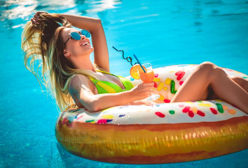 Tycka om solbr?nnakvinnan i bikini p? den uppbl?sbara madrassen i simbass?ngen royaltyfri fotografi