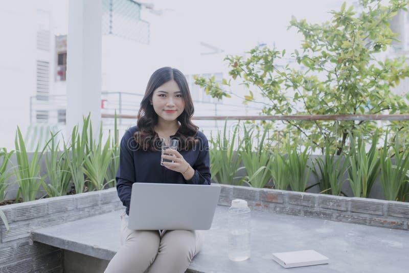 Tycka om trevlig tid p? ny luft H?rlig ung kvinna som arbetar p? hennes b?rbar dator och ler, medan sitta i golv p? hennes utomhu arkivfoto