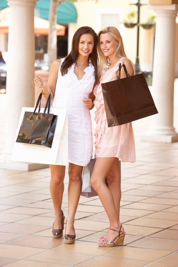 tycka om unga kvinnor för shopping två arkivfoton