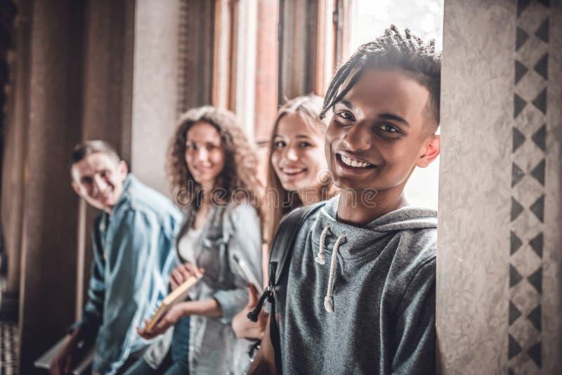 Tycka om universitetliv Stilig ung indisk student och hans vänner som ler och ser kameran royaltyfri fotografi