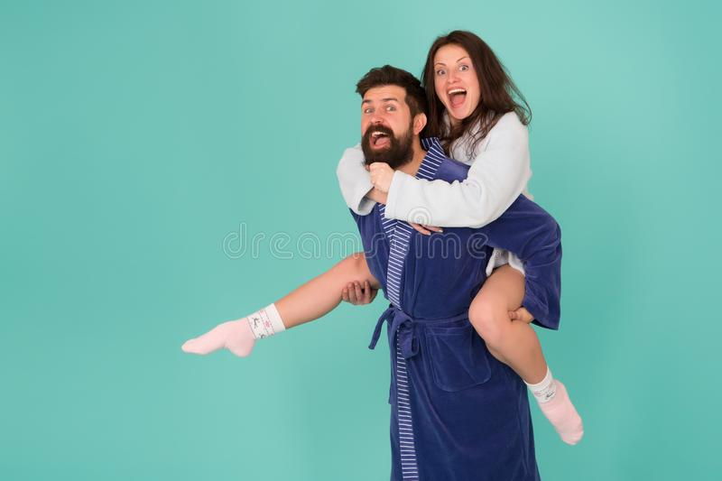Tycka om varje sekund tillsammans Stilig ung man som piggybacking den härliga kvinnan Koppla ihop i badrockar som har gyckel royaltyfria bilder