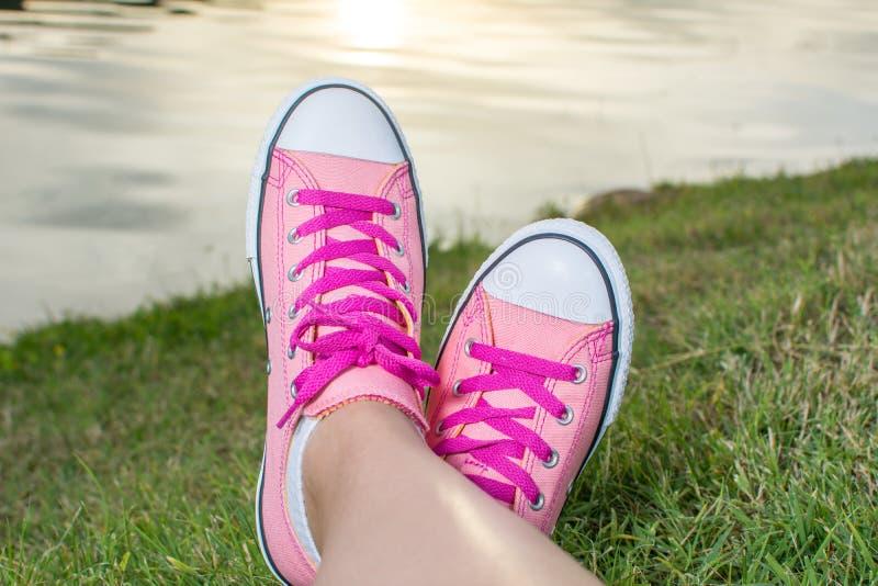 Tycka om vid sjön Kvinna som bär rosa gymnastikskor royaltyfri foto