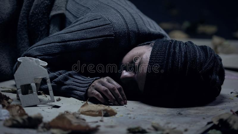 Tycka synd om den sjuka flyktingen som sover på gatan, det närliggande pappershuset, sökande asylbegrepp royaltyfri foto