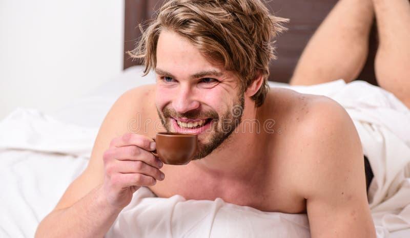 Tycker om den attraktiva utseendemässiga mannen för grabben upp varmt nytt bryggat kaffeslut första smutt Varje morgon med hans k royaltyfri bild