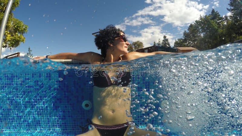 Tycker om den gulliga kvinnan för brunetten vatten i termisk brunnsortsimbassäng royaltyfri foto