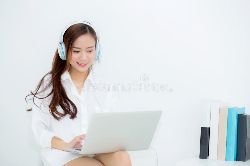 Tycker om den lyckliga asiatiska unga kvinnan för den härliga ståenden, och gyckel lyssnar musik med headphonesammanträde i varda royaltyfria bilder
