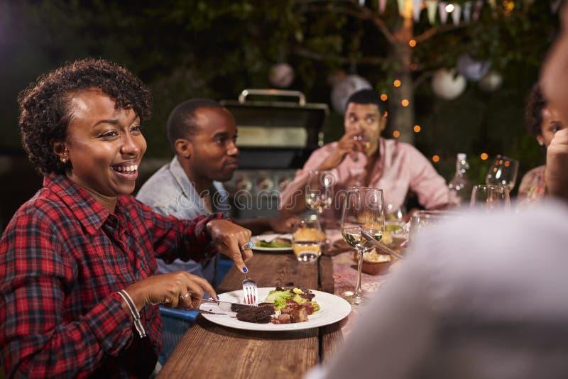 Tycker om den svarta familjen för vuxna människan matställen och konversation i trädgård royaltyfri foto