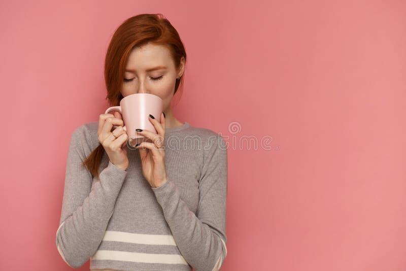 Tycker om den unga kvinnan för rödhåriga mannen med en kopp hennes varma drink arkivfoton