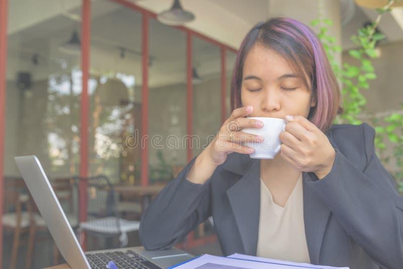 Tycker om stängande ögon för affärskvinna varm cappuccino, medan arbeta royaltyfri foto