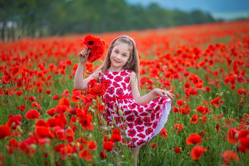 Tycker om tonåriga blåa ögon för skönhet sommardagar Gullig utsmyckad klädd flicka i vallmofält Fält av blommande vallmo arkivfoto