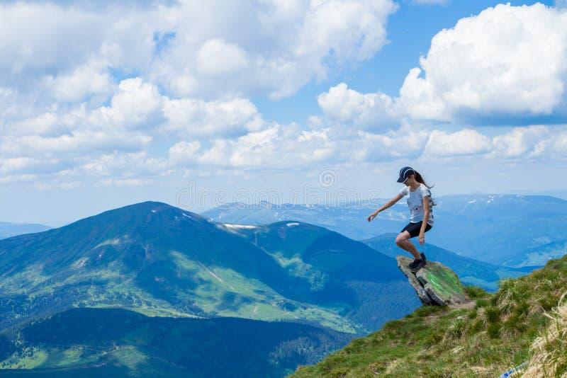 Tycker om turist- sammanträde för den unga kvinnan på kanten för klippa` s av berg och sikten royaltyfri bild
