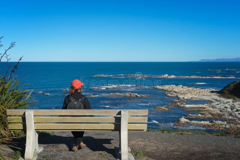 Tycker om turist- sammanträde för kvinnan på en bänk havsikt royaltyfria foton