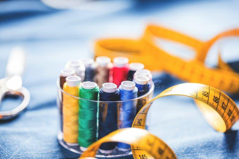 Tyg av olika typer och objekt för att sy Mångfärgat tyg, trådrullar, visare, en sömnad tafsar är nödvändigt för att sy arkivfoton