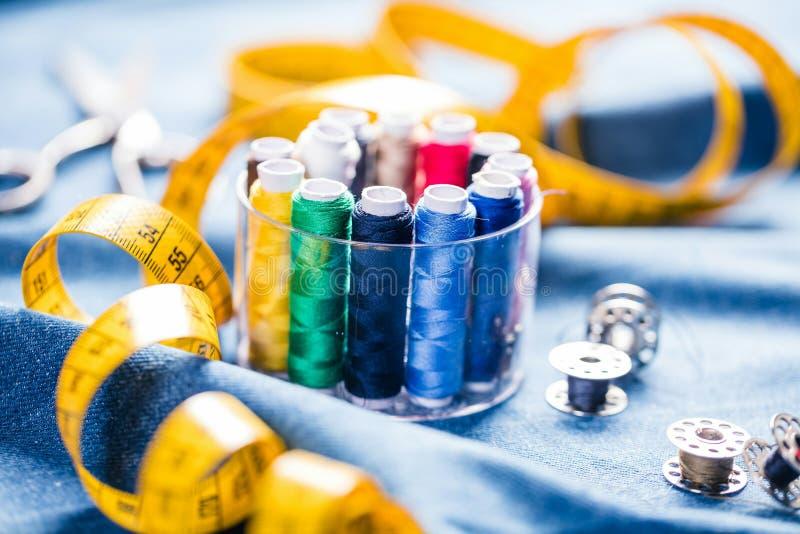 Tyg av olika typer och objekt för att sy Mångfärgat tyg, trådrullar, visare, en sömnad tafsar är nödvändigt för att sy fotografering för bildbyråer