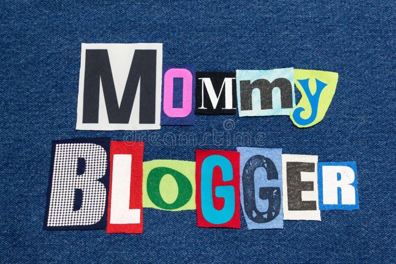 Tyg för collage för ord för MAMMABLOGGERtext färgrikt på blå grov bomullstvill som uppfostrar bloggar och blogging arkivfoto