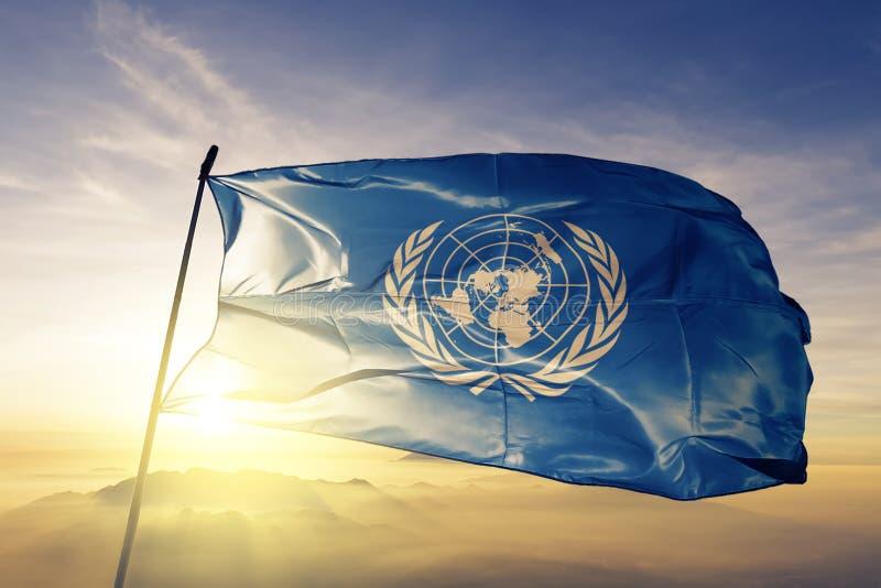 Tyg för torkduk för textil för Förenta NationernaFN-flagga som vinkar på den bästa soluppgångmistdimman stock illustrationer