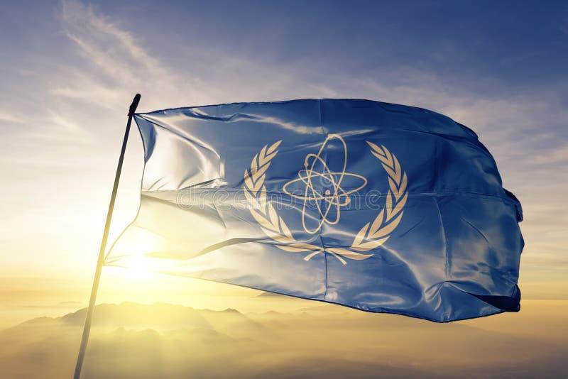 Tyg för torkduk för textil för flagga för IAEA för internationell atomenergibyrå som vinkar på den bästa soluppgångmistdimman vektor illustrationer