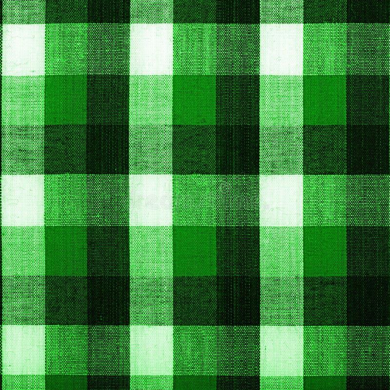 Tyg in i det gröna rastret, en bakgrund arkivfoton