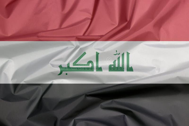 Tygflagga av Irak Veck av irakisk flaggabakgrund royaltyfri bild