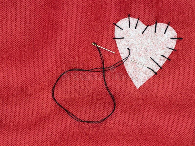 Tyghjärta som är röd med den vita lappen och svartsömnadtråden Begrepp för bruten hjärta för lagning royaltyfria foton
