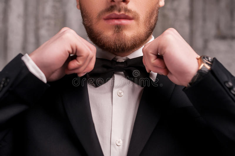 Tying a bow tie. Cropped image of handsome young beard man in formalwear adjusting his bow tie royalty free stock photography