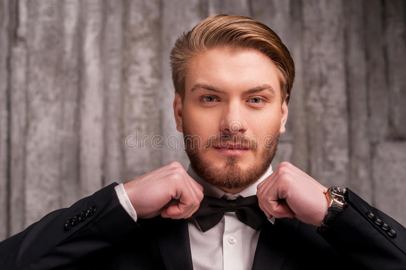Tying a bow tie. Handsome young man in formalwear adjusting his bow tie and looking at camera stock photo
