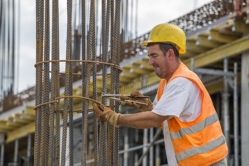 Tying reinforcing steel bars with plier and wire. BELGRADE, SERBIA - SEPTEMBER 08, 2016: Tying reinforcing steel bars with plier and wire on construction pillars stock photography